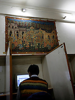 Boy at internet cafe sits under a carpet with historic scenes. Srinagar, Kashmir,India. © Fredrik Naumann/Felix Features
