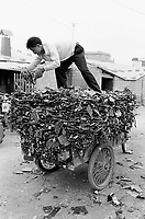 China. Province of Guangdong. The village of Nanmen is part of the town of Guiyu. A man loads his delivery tricycle with printed and integrated circuits of computers which were taken down by workers' hand from old computers. The various parts will be recycled for its electronic components and chips,... © 2004 Didier Ruef