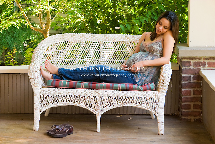 A beautiful young pregnant Hispanic woman relaxing outside white waiting for the birth of her baby.