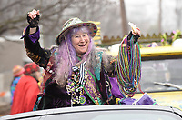 NWA Democrat-Gazette/FLIP PUTTHOFF<br /> MARDIS GRAS ON PARADE<br /> Dixie Rhyne, grand marshal of the Fat Saturday Parade of Fools Mardis Gras parade in Fayetteville, carries a good supply of party beads to toss Saturday Feb. 10 2018 while riding in the the annual parade. Rhyne helped organize the first Fayetteville Fat Saturday parade in 1992. Mardis Gras costumes, Cajun music, and lots and lots of colorful beads were part of the festivities. The parade circled the town square and rolled down Dickson Street.