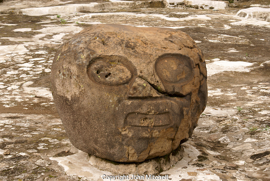 Pre-Columbian stone head in the Patio de los Atares or Patio of the Altars. Archaelogical Zone, Cholula, Puebla, Mexico Cholula is a UNESCO World Heritage Site.