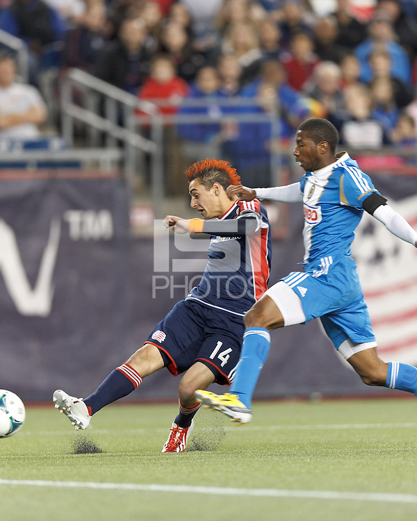 New England Revolution midfielder Diego Fagundez (14) takes a shot as Philadelphia Union defender Raymon Gaddis (28) defends.In a Major League Soccer (MLS) match, the New England Revolution (blue/red) defeated Philadelphia Union (blue/white), 2-0, at Gillette Stadium on April 27, 2013.