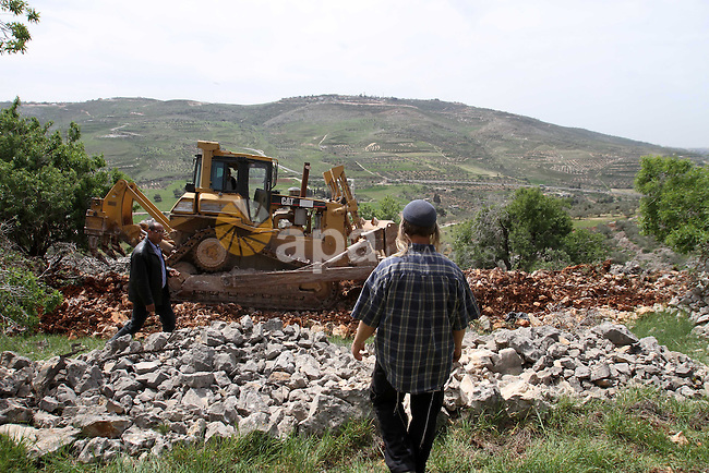 A Jewish settler walks in front Palestinian farmers as they ride their bulldozer in the West Bank village of Burin south of Nablus, March 23, 2014. Clashes broke out Sunday morning after Jewish settlers from the nearby Bracha settlement attacked Palestinian farmers to prevent them from open a road  in their fields. Photo by Nedal Eshtayah