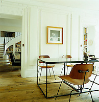 The dining room opens into the library and both have antique bare wooden floorboards
