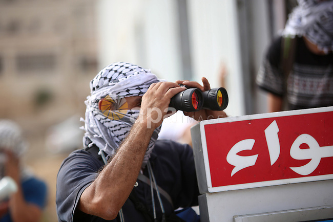 A Palestinian protester looks through binoculars during clashes with Israeli security forces near the Jewish settlement of Bet El, near the West Bank city of Ramallah, on October 13, 2015. A wave of stabbings that hit Israel, Jerusalem and the West Bank this month along with violent protests in annexed east Jerusalem and the occupied West Bank, has led to warnings that a full-scale Palestinian uprising, or third intifada, could erupt. The unrest has also spread to the Gaza Strip, with clashes along the border in recent days leaving nine Palestinians dead from Israeli fire. Photo by Shadi Hatem
