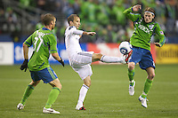 L.A. Galaxy forward Mike Magee,  center kicks the ball away from Seattle Sounders defender Jeff Parke,  left, and midfielder Erik Friberg during play at Qwest Field in Seattle Tuesday March 15, 2011. The Galaxy won the game 1-0.