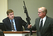 Defense witness David Mcgill, a police officer from Montgomery County, Maryland, watches Prince William County (Virginia) Commonwealth Attorney, Paul S. Ebert, as he holds the Bushmaster rifle during his testimony in the trial of sniper suspect John Allen Muhammad in the Virginia Beach Circuit Court in Virginia Beach, Virginia on November 12, 2003. <br /> Credit: Lawrence Jackson - Pool via CNP