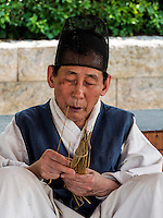 traditioneller Strohflechter mit Kopfbedeckung Tanggon  im Namsangol Hanok Village, Seoul, S&uuml;dkorea, Asien<br /> traditional straw plaiting in Namsangol Hanok village, Seoul, South Korea, Asia
