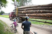 Polish bicycling family encounter logging truck on road. Zawady Central Poland