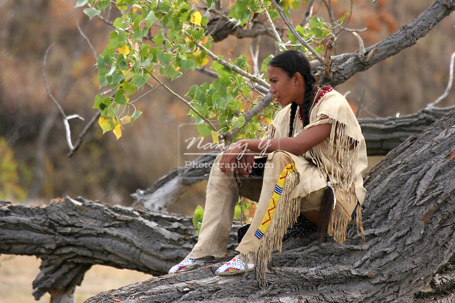 A teenager Native American Indian boy sitting on a downed tree
