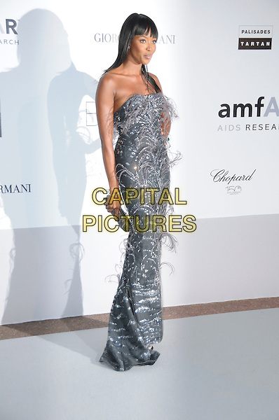 NAOMI CAMPBELL.arrivals at amfAR's Cinema Against AIDS 2010 benefit gala at the Hotel du Cap, Antibes, Cannes, France during the Cannes Film Festival.20th May 2010.amfAR full length long maxi dress silver feathers  strapless  grey gray clutch bag .CAP/CAS.©Bob Cass/Capital Pictures.