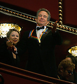Actor Warren Beatty gestures to the crowd from the presidential box with wife Annette Benning (L)  and music legend Elton John (R) prior to the start of the Kennedy Center Honors show at the Kennedy Center December 5, 2004 in Washington, DC. Six honorees were saluted for their lifetime contributions to American culture through the performing arts.  His wife, Annette Bening is at left..Credit: Win McNamee - Pool via CNP