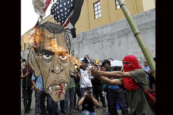 SJS01. SAN JOSÉ (COSTA RICA), 01/05/2013.- Manifestantes queman una imagen mofa del presidente Barack Obama hoy, miércoles 1 de mayo de 2013, durante la marcha por el Día Internacional del Trabajo en San José (Costa Rica). Un enfrentamiento a golpes entre varias decenas de jóvenes y la policía alrededor del Congreso, donde estaban reunidos todos los diputados, cerró la tradicional marcha del 1 de mayo en este país. EFE/Jeffrey Arguedas.