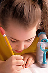 Young girl writing at school studying with microscope