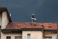 Milano, periferia nord. Lavori di manutenzione sul tetto di un palazzo residenziale sotto un cielo plumbeo --- Milan, north periphery. Maintenance work on the roof of a residential building under a leaden sky