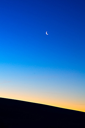 Dawn with waning crescent moon at White Sands National Monument in New Mexico.