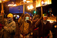 One of the oldest traditions of Mardi Gras, Flambeaux carrying burning kerosene torches line up before parading in the Krewe of Hermes Parade in the Uptown area of New Orleans, Louisiana, USA.