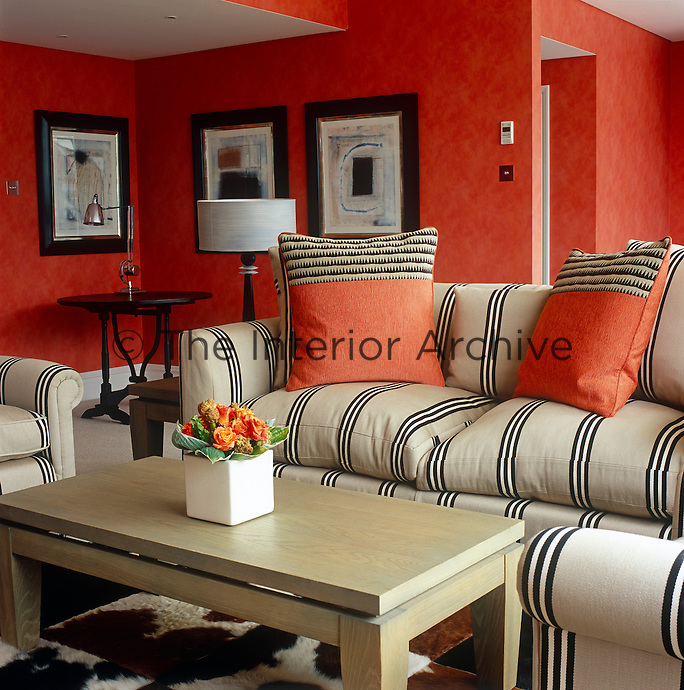 A striking contrast is created between the black and white stripe of the sofa and the red pigment colourwash on the walls of this hotel room in London