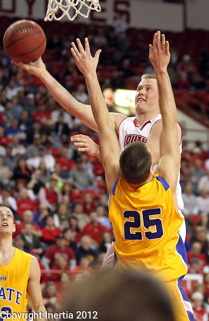 VERMILLION, SD - FEBRUARY 9: Louie Krogman #4 from the University of South Dakota takes the ball to the basket past Chad White #25 from South Dakota State in the second half of their game Thursday night at the DaktaDome in Vermillion, SD. (Photo by Dave Eggen/Inertia)