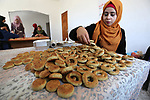 Palestinian women prepare traditional date-filled mini cakes to sell for customers a few days ahead of Eid al-Fitr holiday in Dair Al Balah, in the center of Gaza Strip on June 12, 2018. Eid al-Fitr marks the end of Muslim's holy fasting month of Ramadan when faithfuls abstain from eating, drinking, smoking and sexual activities from dawn to dusk. Photo by Ashraf Amra
