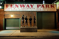 """A statue entitled """"Teammates"""" by Antonio Tobias Mendez featuring the likenesses Ted Williams, Johnny Pesky, Bobby Doerr and Dom DiMaggio, stands outside of Gate B at Fenway Park in Boston, Massachusetts, USA, on the night before the 2011 season opener of the Boston Red Sox."""
