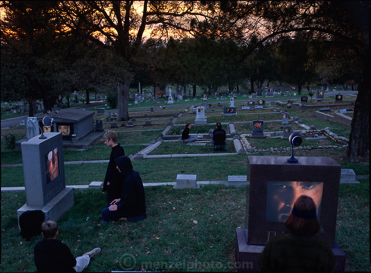 """FINAL CONTACT: """"GRAVEWATCH"""".  Photo Illustration for the Future of Communication GEO (Germany) Special issue. Fictional Representation and Caption: Interactive gravestones became quite popular in the 21st century. Adding snippets of video of the diseased was quite easy to program since nearly every family had extensively documented their family time with small digital videocams. AI (artificial intelligence) computer programs made conversations with the dead quite easy. These virtual visits to the underworld became passé within a decade however, and graveyard visits became less common. By mid-century many people wanted to insure that their relatives would continue paying their respects, and keeping their memory alive. New technology insured regular visits to the gravesite to pick up a monthly inheritance check issued electronically by a built-in device with wireless connection to the living relative's bank account. Face recognition (and retinal scanners on high-end models) insured that family members were present during the half-hour visits. A pressure pad at the foot of the grave activated the system and after 30 minutes of kneeling at the grave, watching videos or prerecorded messages or admonitions, a message flashed on the screen, indicating that a deposit had been made electronically to their bank account. For the Wright family of Napa, California, there is no other way to collect Uncle Eno's inheritance other than by monthly kneelings. [""""Gravewatch"""" tombstones shown with """"Retscan"""" retinal scanning ID monitors.] MODEL RELEASED"""