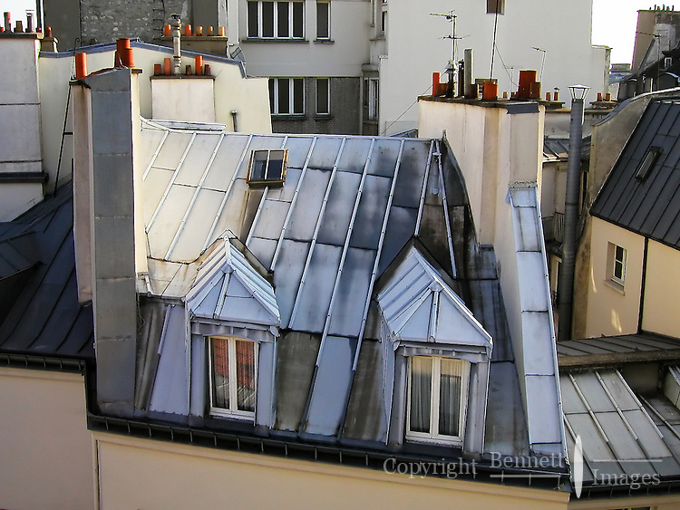 The morning sun illuminates the angled rooftops of central Paris, France.