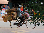 Man on Bike Selling Woven Goods, Cambodia