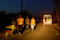 A group of people, one of whom is pushing their belongings in a wheelbarrow, arriving at Zaatari Refugee Camp in the night. Meanwhile leaving the camp is a boy getting a clandestine ride out on the back of an ambulance. Approximately two million people have fled the conflict in Syria. At least 130,000 of them live in Zaatari Refugee Camp, although it was designed to house 60,000, and a further 2,000 people arrive each day.