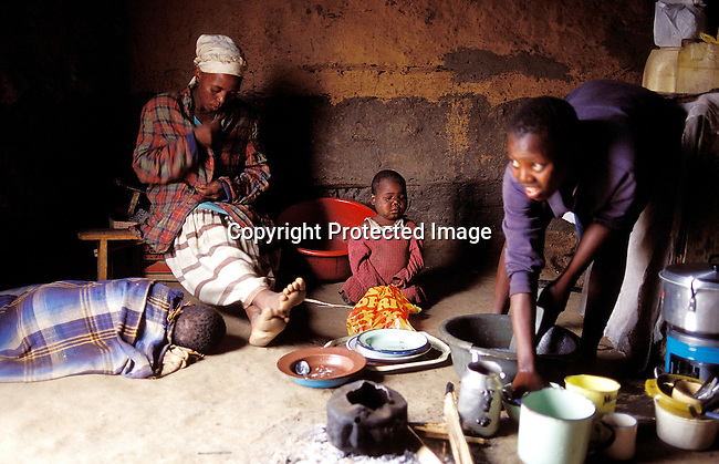 PIFAMIL50079.People. Family. Kwa Zulu Natal. Young girl washing dishes in a plastic bucket. Her mother sits on a bench with two of her children at her feet. One child wrapped in blanket , sleeping. '99. Pot, paraffin/gas stove. Extreme poverty.©Per-Anders Pettersson/iAfrika Photos