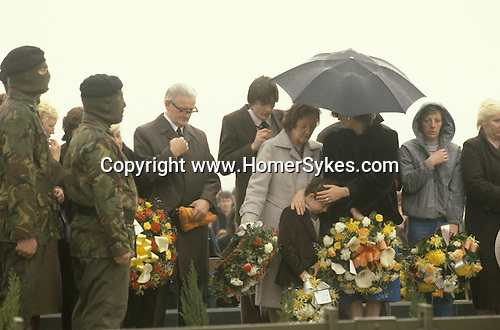 """Bobby Sands """"Robert Gerard Sands"""" funeral  his mother in pale coat, wife Geraldine Noade with hands to head of their son Gerard who looks down. 1981 Milltown cemetery Northern Ireland UK"""