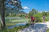 Germany, Bavaria, Swabia, East-Allgaeu, Fuessen: district Weissensee-Oberkirch at Lake Weissensee with daughter church St. Nikolaus, two men on a cycling trip | Deutschland, Bayern, Schwaben, Ost-Allgaeu, Fuessen: Ortsteil Weissensee-Oberkirch am Weissensee mit Filialkirche St. Nikolaus, zwei Maenner machen eine Radtour