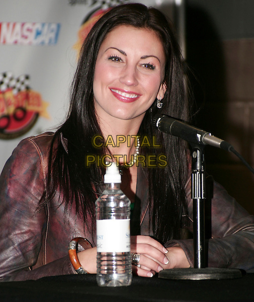 DANIELLE PECK .Fifth Annual Celebration of Music and Motorsports Sprint Speed and Sound Press Conference, Nashville, Tennessee, USA, 8th January 2010..half length water bottle sitting smiling microphone .CAP/ADM/EM.© Eddie Malone/AdMedia/Capital Pictures.