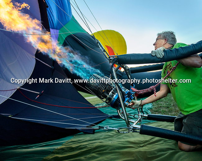 A near record crowd hot air balloon fans filled the hillsides at the National Balloon Classic launch field July 30 for a fly-in and Night Glow. Balloonist Dave Reineke of Mahomet, Illinois fires up his burner to fill the balloon with hot air. He flies the Parrot balloon.