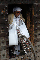 A man struggles to get his bicycle and its cargo through one of the narrow gates of the Old City of Lahore.