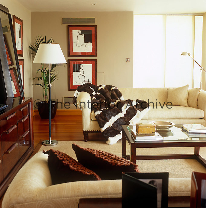 Warm tones of brown and oatmeal in the sofas and wooden furniture have combined to create this comfortable living room