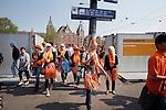 Amsterdam, 30 april 2011.Koninginnedag: feestvierders arriveren via Amsterdam Centraal Station in de stad..Foto Felix Kalkman
