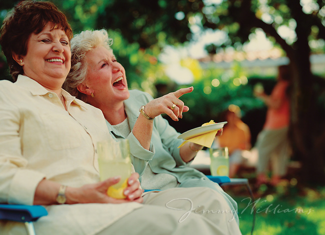 Two women laugh together at a botanical garden