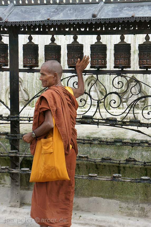 monk in saffron garment turning the prayer wheels in buddhist temple Swayambhu in Kathmandu, Nepal, September 2011. Inside the metalwork prayer wheels are long text-rolls covered with scripture of prayers.