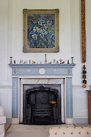An oil painting of flowers hangs above an Adam fireplace in the master bedroom