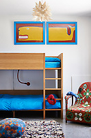 The children's room has a set of bunk beds with blue bedding and colourful prints, armchair and rug.
