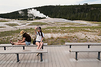 A woman takes a selfie on the boardwalk next to Old Faithful after the geyser erupted in Yellowstone National Park, Wyoming, USA. In the days surrounding when this image was taken, the geyser averaged an eruption about every 90 minutes, though occasionally there were hours between eruptions.