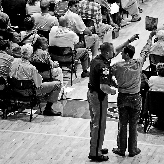 A Charles County, Md., Sheriff's deputy grabs a LaRouce publication featuring a Hitler-mustached Obama from a man at North Point High School in Waldorf, Md., on Sept. 1, 2009, during House Majority Leader Steny Hoyer's town hall meeting at the school. Signs and posters were not allowed inside the event.