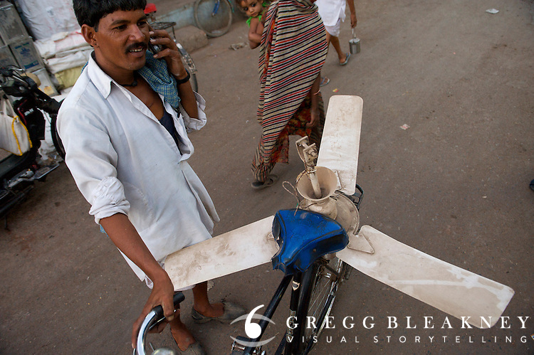 A villager uses his bike to take a spent fan into the city for repair.