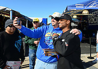 Oct. 26, 2012; Las Vegas, NV, USA: NHRA top fuel dragster driver Antron Brown poses with a fan during qualifying for the Big O Tires Nationals at The Strip in Las Vegas. Mandatory Credit: Mark J. Rebilas-