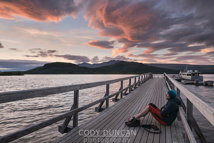Hiker watches sunset from pier on lake at STF Saltoluokta Fjällstation, Kungsleden trail, Lapland, Sweden