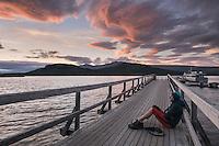 Hiker watches sunset from pier on lake at STF Saltoluokta Fjällstation, Kungsleden trail, Lapland, Sweden