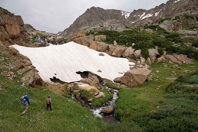 couple hiking, (MR), hike, subalpine, snow bank, stream, meadow, Rowe Mountain, high elevation, recreation, outdoors, activity, adventure, back country, August, afternoon, Rocky Mountain National Park, Colorado, USA