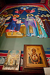 Two old icons on the wall beneath a fresco depicting Serbian Orthodox history at St. Sava Church, Jackson.