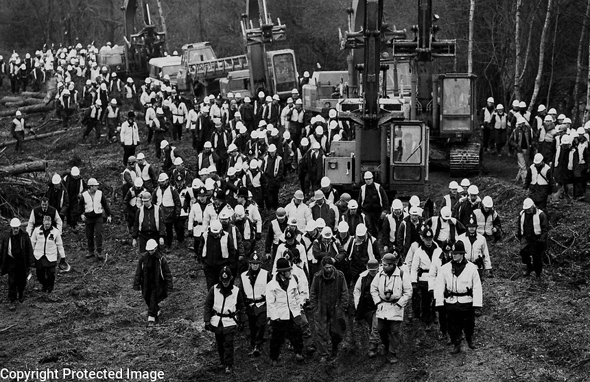 Caption:Hundreds of security guards and police guard diggers <br /> that have been clearing woodland to make way for the bypass. <br /> There is one protester (front row middle) accompanying them. <br /> Newbury,Berkshire,March 1996.<br /> <br /> Photographer:Andrew Testa<br /> <br /> Title:Newbury 8<br /> <br /> Credit:&copy;Andrew Testa